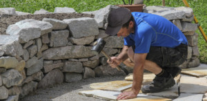 landscaper laying down informal patio stone
