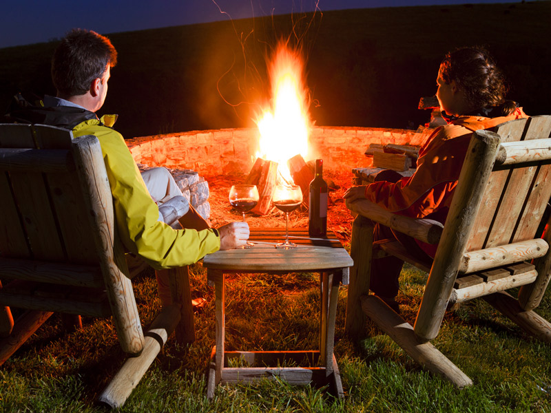 couple around a firepit in early fall